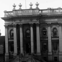 Image: A large rectangular building with two storeys and numerous columns in the Greek revival style