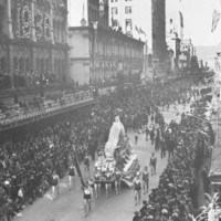 Image: parade of floral floats on street with crowds of people watching.