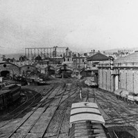 Image: a view of a busy railway yard with a number of parked carriages on a series of tracks. In the background are a series of curved roof buildings.