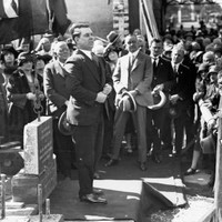 Image: a large crowd gathers around a man in a 1920s era dark suit who stands on am small stage with a carved foundation stone.