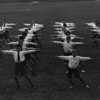 Image: boys in lines on oval with arms outstretched