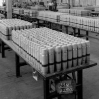 Image: A group of men and women stand in a large room full of rows of tables. Atop each table are several rows of artillery shells