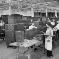 Image: A group of women and two men stand at tables in a large room and manufacture rectangular metal containers
