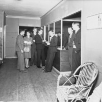 Image: people standing at reception desk
