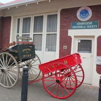 Image: Restored horse-drawn cart outside of a historical society building.