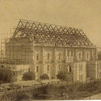 Image: A large hall is under construction. The stone walls are covered in scaffolding and the hammerbeams of the roof are visible. Men can be seen on the roof of the building.