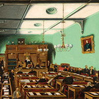 Image: Men in black suits sit in a green painted room, on red chairs at wooden desks facing a wooden construction with raised speaker's chair and built in bookcases. The top of this area also serves as a public gallery.