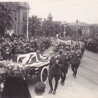 Image: A flag covered casket proceeding past onlookers