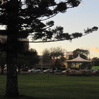 Image: A grassy park interspersed with trees and a single wooden gazebo. A large road with several cars and a number of large buildings are visible in the background