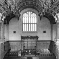 Image: the interior of a large hall with stone and wood panneled walls and a decorative wooden ceiling. The rear wall features a large window underneath which is a stage area with rows of chairs upon it and more chairs facing it.