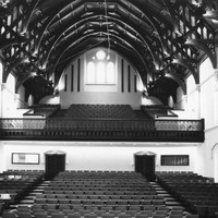Image: The interior of a large hall with a hammerbeam roof and tiered seating on two levels.