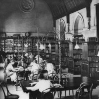 Image: male and female students sit at tables in a library with a vaulted ceiling