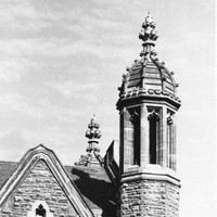 Image: a stone tower with a decorative domed roof rises above a simpler pitched slate roof.