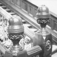 Image: A close up image of decorative carving on the newels (and the knobs that top them) of a large staircase