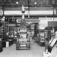 Image: Glass cases inside a building containing a variety of exhibits, and advertising signage, a man stands to the left dressed in uniform