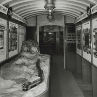 Image: The interior of a train carriage containing a railway model, and walls lined with information panels about railways