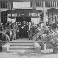 Image: a group of men and women in early 20th century dress sit or stand in front of a doorway in the shade of a verandah decorated by flags. Palms in pots next to the stairs leading to the verandah dominate the foreground.