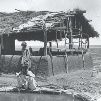 Image: Three men crouch near a pool next to a small, thatch-roofed structure in a remote area