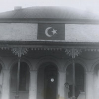 Image: An Islamic symbol of a crescent moon and star is painted just below the roof on a building fronted with arches. A man bends down behind a narrow column with one leg bent at the knee, possibly removing or putting on a shoe.