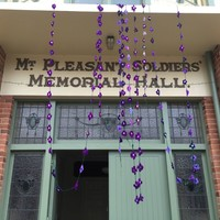 Image: garlands of crocheted violets hanging from building entrance