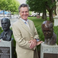 Image: Man standing between two bronze busts