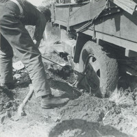 Image: A young Caucasian man in utility clothing uses a vehicle jack to attempt to extricate the bogged down rear wheel of a 1930s vintage utility truck