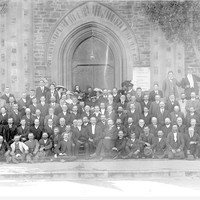 Image: Black and white group photograph of over 150 people. There are five rows of people, mostly men, standing in front of a church
