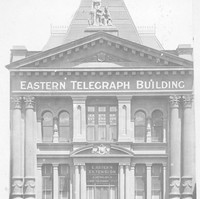 """Image: Photograph of the front of a building. It has several columns and reads """"Eastern Telegraph Building"""""""