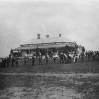 Image: Black and white photograph of a gathering of people. Some are standing on the verandah of a house. Another groups stands further back from the house (closer the camera) in a large circle, joined by their hands