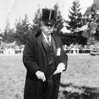 Image: A middle-aged man wearing a suit with top hat and holding a cane stands in a paddock. A fence and buildings are visible in the background