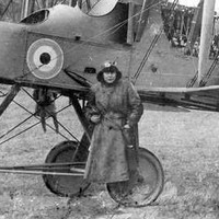 Image: A man in a First World War-era flying outfit stands in front of a British Royal Air Force biplane