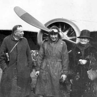 Image: A man in First World War-era aviator attire stands in front of an aircraft with two men and two women