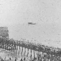 Image: A large crowd of people watch an early twentieth century aircraft make a low pass over a jetty near a seaside community