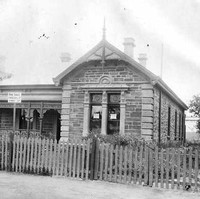 Image: A large stone cottage with iron lacework surrounding its front verandah