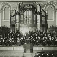 Image: An orchestra poses for a photograph on a stage in front of a large pipe organ