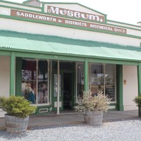 Image: Colour photo of a building's façade with cream and green colour scheme, a museum sign features on the front.