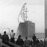 Image: A large iron ship a short distance from shore shortly after being launched. Several men on shore in the foreground look at the ship