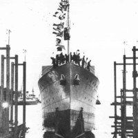 Image: A large iron warship is launched into the water. Several men stand on the bow of the ship, which is festooned in flags