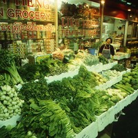 Image: woman standing with large display of vegetables in front of Asian grocery store