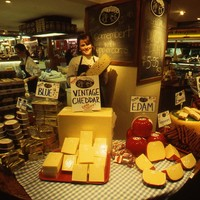 Image: woman standing surrounded by cheese in market stall