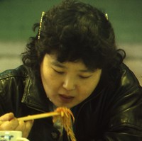 Image: woman eating noodles with chopsticks