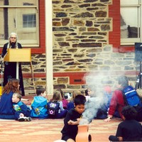 Image: children at event with smoking fire in centre