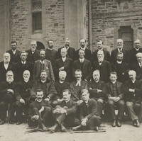 Image: A group portrait of ministers in front of a stone church. There are four rows, two standing, two sitting of 28 people.