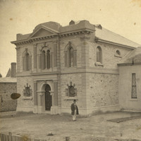Image: Two large interconnected synagogue buildings, a man stands in the bare yard at the front of the building.