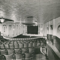 Image: Inside of a theatre hall, view of a front stage overlooking rows of chairs and a balcony