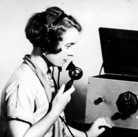 Image: A Caucasian woman in a 1930s-era dress sits at a table upon which sits a large radio set. The woman wears a headset and holds the radio receiver