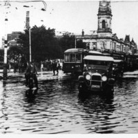 Image: View of Victoria Square showing motorcars, a motorbike rider and the electric trams navigating the flooded streets through Victoria Square in 1925