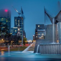 Image: Three Rivers Fountain which is located in Victoria Square, Adelaide.  This photo was taken at night time, with tall buildings in the background.