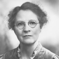 Image: Portrait photograph of a woman wearing glasses