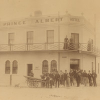 Image: A group of men standing in front of the Prince Albert Hotel. Three women are standing on the balcony.